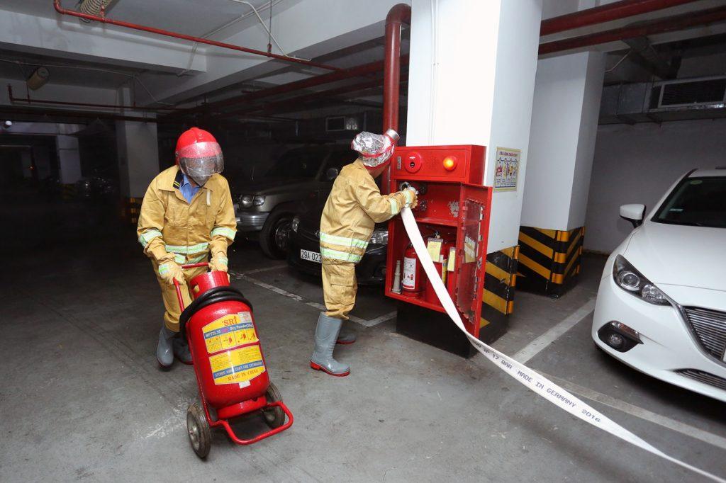 Bạn cần tìm kiếm và sử dụng bình cứu hỏa để khống chế đám cháy bãi giữ xe